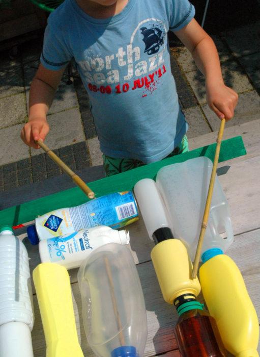 kind trommelt op gerecycled materiaal in een workshop voor het primair onderwijs